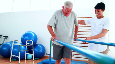 Smiling physiotherapist helping patient walk with... Stock Video Footage