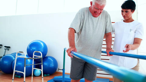 Smiling physiotherapist helping patient walk with parallel bars Footage