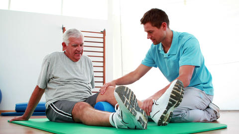 Physiotherapist helping patient with his knee mobility Stock Video Footage