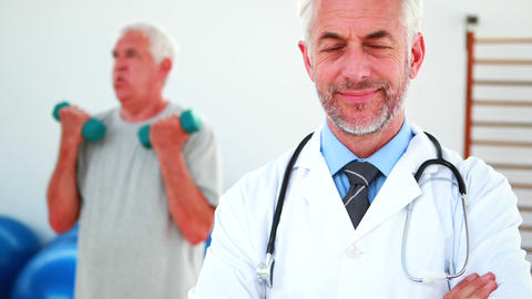 Smiling doctor looking at camera with patient exercising... Stock Video Footage