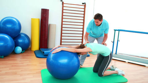 Trainer helping his client stretch her back with exercise... Stock Video Footage