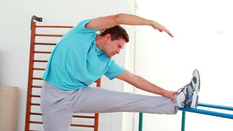 Flexible man stretching his leg Stock Video Footage