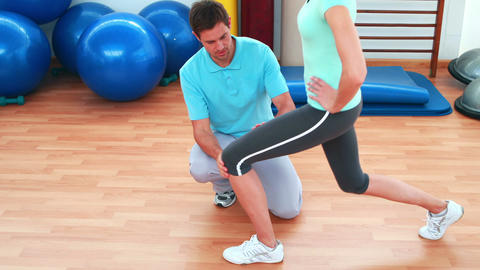 Trainer showing his client how to do a lunge correctly Stock Video Footage
