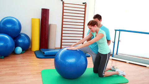 Trainer helping his client stretch her back with exercise ball Footage