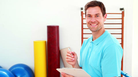 Smiling Physical Therapist Writing On Clipboard stock footage