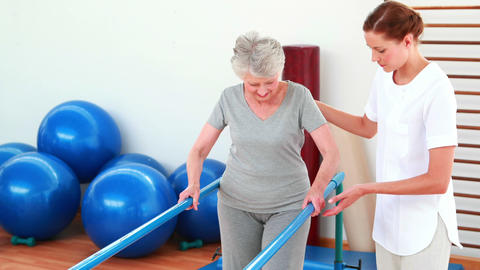 Physical therapist helping patient walk with parallel bars Footage
