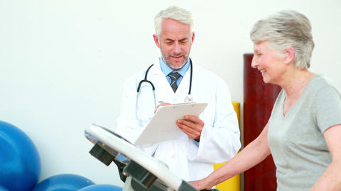 Doctor watching patient using treadmill Stock Video Footage