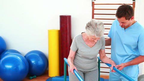 Physical therapist helping patient to walk with parallel bars Footage