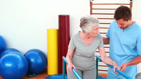 Physical therapist helping patient to walk with parallel... Stock Video Footage