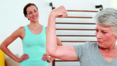 Trainer watching proud elderly client flexing her bicep Footage