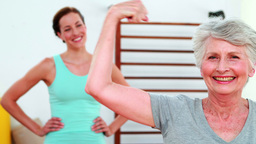 Trainer watching proud elderly client flexing her bicep Stock Video Footage