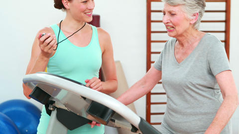 Trainer watching elderly client using treadmill Footage