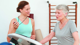 Trainer watching elderly client using treadmill Stock Video Footage