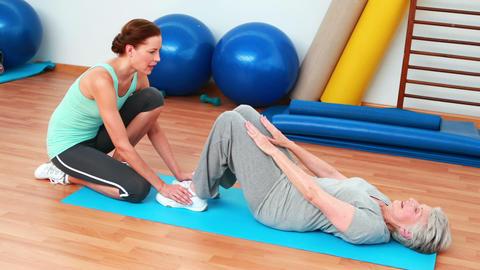 Trainer helping her elderly client do sit ups Footage