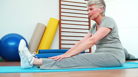 Elderly woman touching her toes on exercise mat Footage