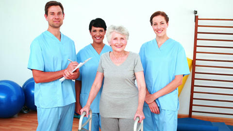 Elderly woman smiling with her physical rehab team Stock Video Footage
