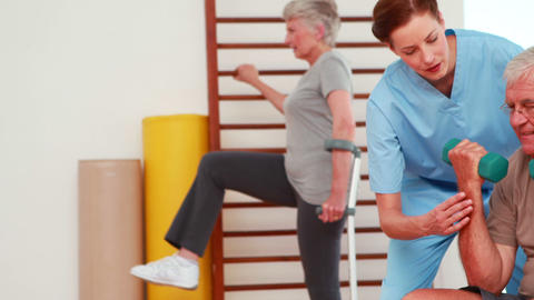 Senior citizens exercising with physiotherapist Stock Video Footage