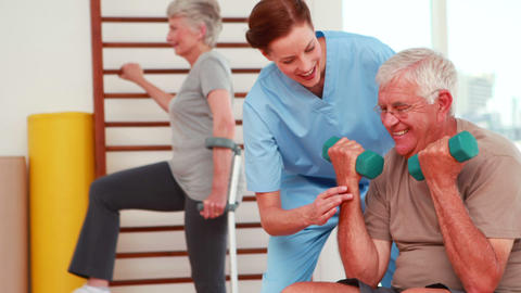 Senior citizens exercising with physiotherapist Footage