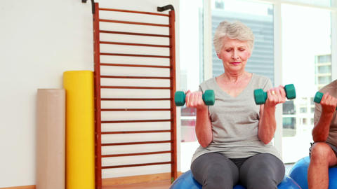 Two senior citizens working with physiotherapist Stock Video Footage
