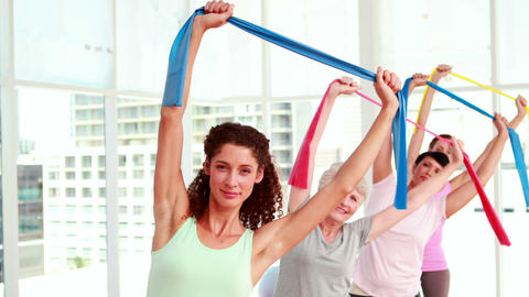 Women stretching resitance bands at a fitness class Stock Video Footage