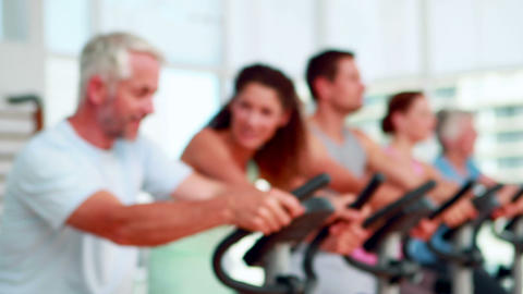 Happy group doing a spinning class with trainer smiling... Stock Video Footage