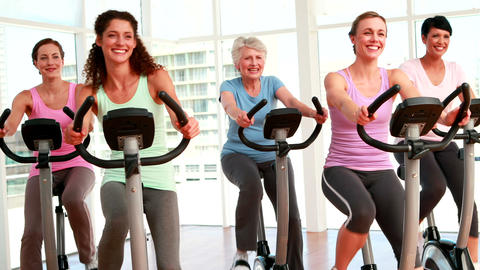 Group of smiling women in doing a spinning class Stock Video Footage