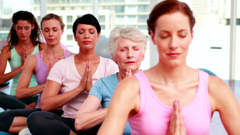 Group of peaceful women in fitness studio doing yoga Stock Video Footage