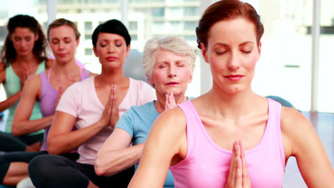 Group of peaceful women in fitness studio doing yoga Footage
