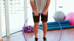 Fit man jumping through a hula hoop Stock Video Footage