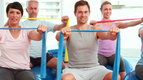 Group sitting on exercise balls stretching resistance bands Stock Video Footage