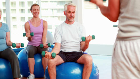 Exercise class sitting on exercise balls lifting hand weights Live Action