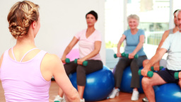Fitness class sitting on exercise balls lifting hand weights Footage