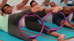 Pilates class lying down using pilates rings Stock Video Footage