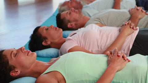 Yoga class lying down in relaxation with eyes closed Footage