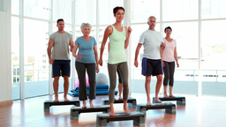 Aerobics class stepping together Stock Video Footage
