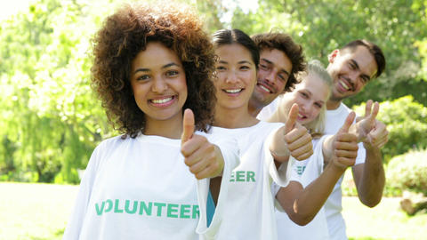 Volunteers standing in a row giving smiling at camera Stock Video Footage