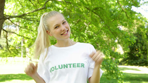 Pretty blonde volunteer dancing and smiling at the camera Stock Video Footage