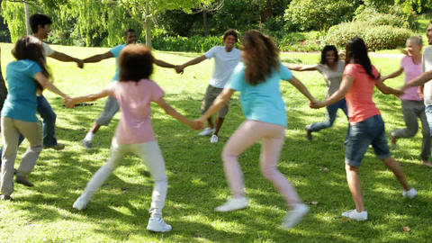 Group of casual young friends playing ring a ring a rosie Stock Video Footage