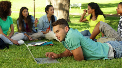 Smiling student using his laptop in front of his friends Stock Video Footage