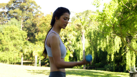 Gorgeous fit brunette lifting dumbbells in the park Footage