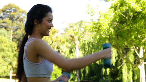 Smiling focused brunette lifting dumbbells in the park Stock Video Footage