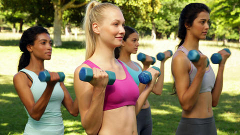 Fitness class lifting hand weights in unison Stock Video Footage