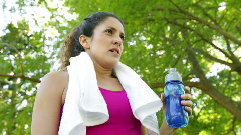 Woman wiping her brow and drinking water after workout in... Stock Video Footage