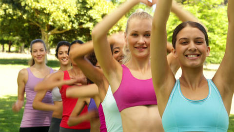 Fitness class stretching their arms and smiling at camera... Stock Video Footage