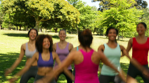 Fitness class doing star jumps together Stock Video Footage