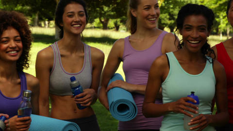 Fitness class smiling at camera before their workout in the park Footage