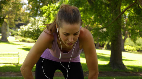 Runner taking a break to drink water in the park Stock Video Footage