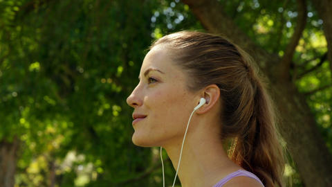 Runner drinking water and listening to music in the park Footage