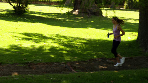 Runner stopping to stretch out in the park Stock Video Footage