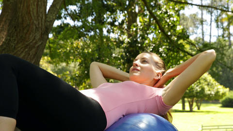 Fit woman doing sit ups on exercise ball in the park Stock Video Footage